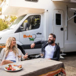 motorhome hire couple sitting relaxing drinking and eating wine strawberries
